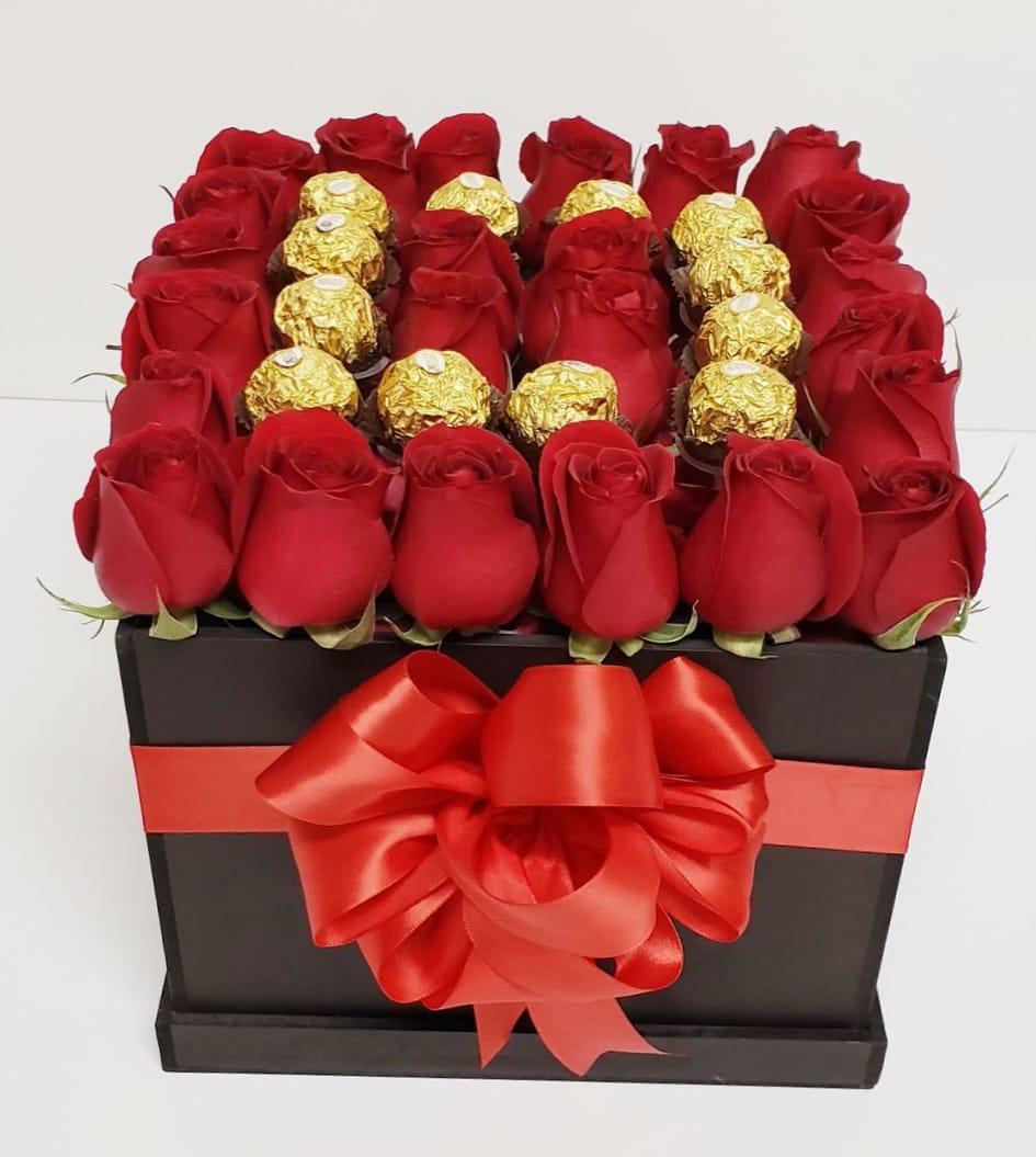 Cubo negro con cinta de tela roja y 25 rosas roja y chocolates ferreros